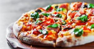 Пицца с сыром моццареллы, ветчиной, перцем, оливкой, мясом, томатным соусом, специями и свежим базиликом Итальянская пицца на дер стоковая фотография rf
