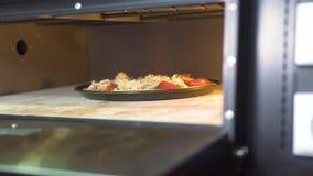 Пицца с сыром, томатами и pepperoni печь в горячей плите на итальянской кухне ресторана Традиционный варить пиццы акции видеоматериалы