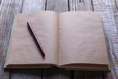 Пишите и книга на деревянной таблице для концепции дела или образования Стоковое Изображение RF