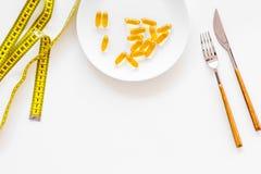 Пищевая добавка для благополучия Рыбий жир или капсулы omega-3 на ленте плиты близко измеряя на белой предпосылке покрывают Стоковое фото RF