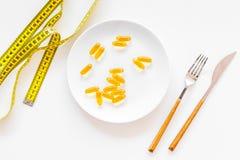 Пищевая добавка для благополучия Рыбий жир или капсулы omega-3 на ленте плиты близко измеряя на белой предпосылке покрывают Стоковая Фотография