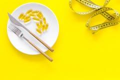 Пищевая добавка для благополучия Рыбий жир или капсулы omega-3 на ленте плиты близко измеряя на желтой предпосылке покрывают Стоковые Фото