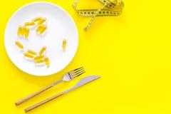 Пищевая добавка для благополучия Рыбий жир или капсулы omega-3 на ленте плиты близко измеряя на желтой предпосылке покрывают Стоковое Фото