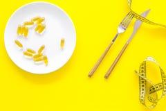 Пищевая добавка для благополучия Рыбий жир или капсулы omega-3 на ленте плиты близко измеряя на желтой предпосылке покрывают Стоковые Изображения