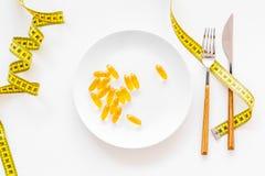 Пищевая добавка для благополучия Рыбий жир или капсулы omega-3 на ленте плиты близко измеряя на белой предпосылке покрывают Стоковые Изображения