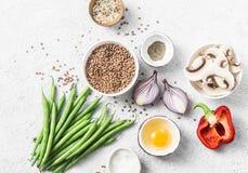 Пищевые ингредиенты плоского положения здоровые вегетарианские для обеда на светлой предпосылке, взгляд сверху Гречиха, зеленые ф Стоковые Изображения