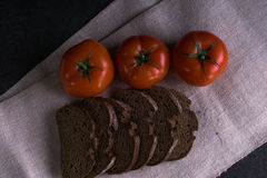 Пищевые ингредиенты предпосылки на скатерти Свежие томаты и домодельный хлеб Стоковое Изображение