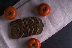 Пищевые ингредиенты предпосылки на скатерти Свежие томаты и домодельный хлеб Стоковые Фотографии RF