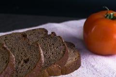 Пищевые ингредиенты предпосылки на скатерти Свежие томаты и домодельный хлеб Стоковые Фото