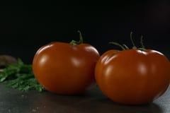 Пищевые ингредиенты предпосылки на черной таблице Свежие томаты и травы, домодельный хлеб Стоковое фото RF