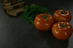 Пищевые ингредиенты предпосылки на черной таблице Свежие томаты и травы, домодельный хлеб Стоковое Изображение RF