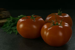 Пищевые ингредиенты предпосылки на черной таблице Свежие томаты и травы, домодельный хлеб Стоковые Фотографии RF
