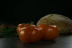Пищевые ингредиенты предпосылки на черной таблице Свежие томаты, травы и домодельный хлеб Стоковые Фотографии RF