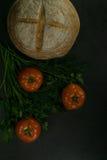 Пищевые ингредиенты предпосылки на черной таблице Свежие томаты, травы и домодельный хлеб Стоковое фото RF
