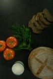 Пищевые ингредиенты предпосылки на черной таблице Свежие томаты, травы и домодельный хлеб Стоковая Фотография