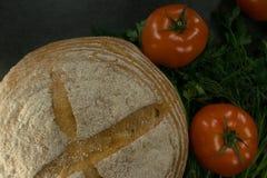 Пищевые ингредиенты предпосылки на черной таблице Свежие томаты, травы и домодельный хлеб Стоковые Изображения