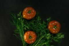 Пищевые ингредиенты предпосылки на черной таблице свежие томаты трав Стоковые Фотографии RF