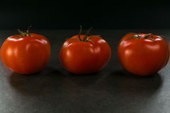 Пищевые ингредиенты предпосылки на черной таблице Свежие томаты, Стоковые Фото