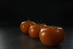 Пищевые ингредиенты предпосылки на черной таблице Свежие томаты, Стоковые Фотографии RF
