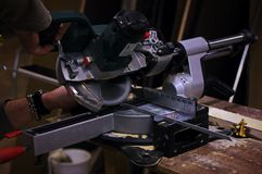 пила конца циркуляра лезвия снятая вверх Человек используя круглую пилу для угла металла V2 Стоковое фото RF