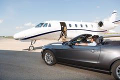 Пилот в автомобиле с откидным верхом припаркованном против частного самолета Стоковое Изображение