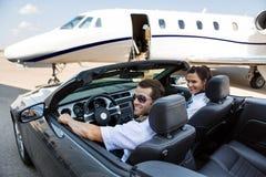 Пилот и стюардесса в автомобиле с откидным верхом против Стоковые Фотографии RF
