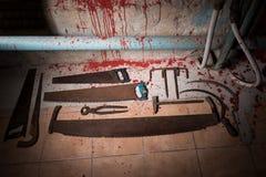 Пилы, схваты и другие приборы на кровопролитном поле в подвале w стоковая фотография