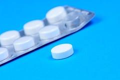 Пилюльки аспирина на голубой предпосылке Стоковые Изображения