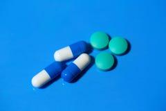 Пилюльки Белые медицинские пилюльки на голубой предпосылке стоковое фото