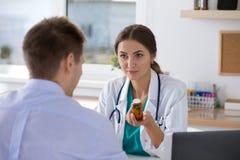 Пилюльки женского доктора медицины предписывая к ее мужскому пациенту Стоковая Фотография