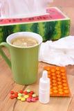 Пилюльки и падения носа для холодов, носовых платков и горячего чая с лимоном Стоковая Фотография