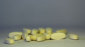 Пилюльки на белой предпосылке символическое фото для медицины и dru Стоковая Фотография