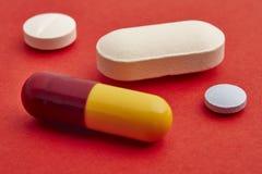 Пилюльки над красной предпосылкой Обработка Medicament здоровье внимательности рукояток изолировало запаздывания Стоковая Фотография