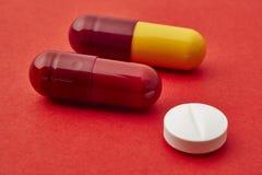 Пилюльки над красной предпосылкой Обработка Medicament здоровье внимательности рукояток изолировало запаздывания Стоковая Фотография RF