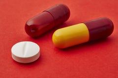 Пилюльки над красной предпосылкой Обработка Medicament здоровье внимательности рукояток изолировало запаздывания Стоковое фото RF