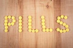 Пилюльки надписи сделанные из желтых медицинских таблеток, концепции здравоохранения Стоковое фото RF