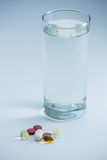 Пилюльки около стекла воды Стоковое Изображение RF