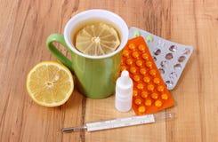 Пилюльки, падения носа и горячий чай с лимоном для холодов, обработка гриппа и жидкое Стоковые Фото