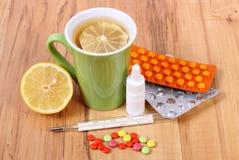 Пилюльки, падения носа и горячий чай с лимоном для холодов, обработка гриппа и жидкое Стоковое фото RF