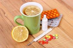 Пилюльки, падения носа и горячий чай с лимоном для холодов, обработка гриппа и жидкое Стоковые Изображения