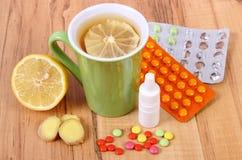 Пилюльки, падения носа и горячий чай с лимоном для холодов, обработка гриппа и жидкое Стоковое Изображение