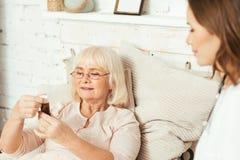 Пилюльки полезного ассистента общественной нагрузки предлагая к пенсионеру дома стоковые изображения rf
