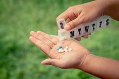 Пилюльки руки женщины лить от коробки напоминания пилюльки в ее руку Стоковое Изображение RF