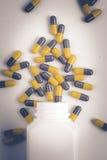 Пилюльки capsules бутылка пилюльки на белой предпосылке Стоковое Фото