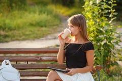 ПК кофе питья девушки и таблетки владением Стоковая Фотография