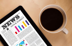 ПК таблетки показывает новости на экране с чашкой кофе на столе Стоковые Фото