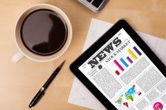 ПК таблетки показывает новости на экране с чашкой кофе на столе Стоковые Фотографии RF