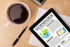 ПК таблетки показывает новости на экране с чашкой кофе на столе Стоковые Изображения RF