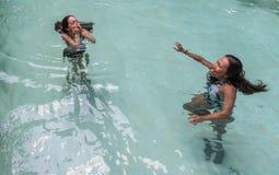 Плавание матери и дочери в бассейне стоковое фото