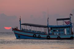 Плавание шлюпки во время захода солнца в океане Стоковые Фотографии RF